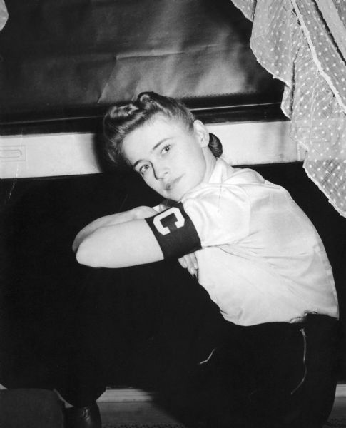 Dickey Chapelle seated by an open window, wearing the correspondent arm band. Taken at time of her first recognition by the War Department as <i>Look's</i> photographer.
