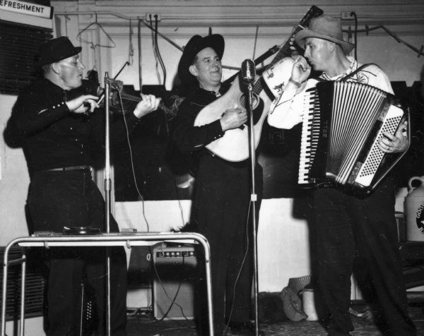 "The Goose Island Ramblers (left to right): George Gilbertsen on fiddle, ""Wendy"" Whitford on guitar, and Bruce Bollard on jug and piano accordion."