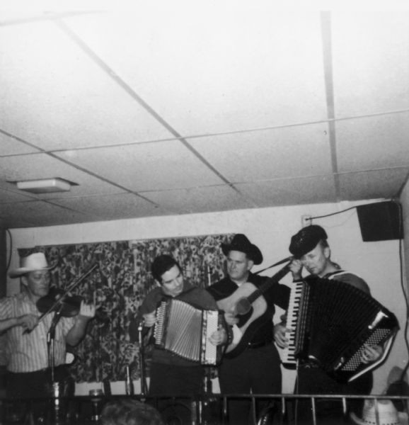 The Goose Island Ramblers performing at Johnny's Packers Inn.  Their instruments include accordions, guitar, and a fiddle. Tommy McDermott sits in on a button accordion.