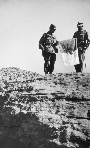Two soldiers hold a flag decorated with a crescent and a star.