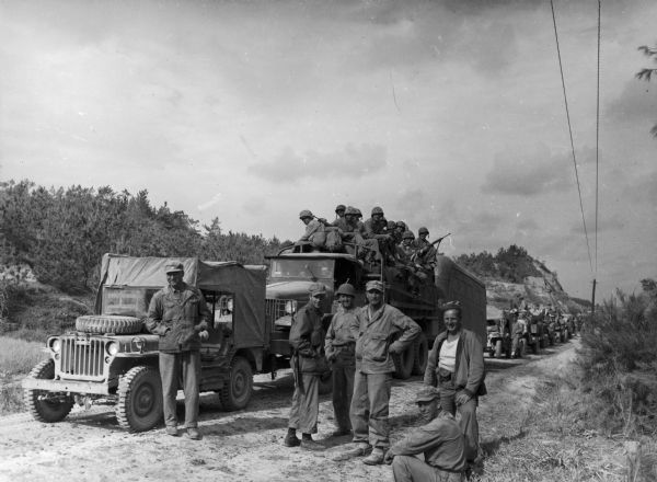 Soldiers pose in front of a military convoy.