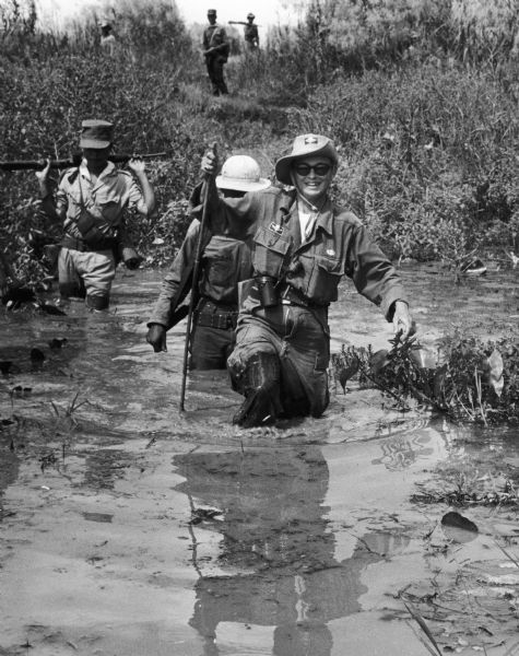 Dickey Chapelle dressed in military clothing wading through a swamp in Vietnam.