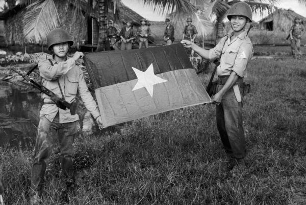Two members of the Sea Swallows display a captured Viet Cong flag. Vietnam.