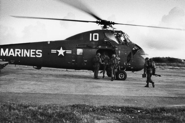 "Uniformed men board helicopter with ""Marines"" on the side."