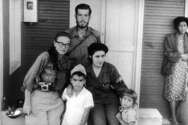 Dickey Chapelle poses with Vilma Espin, who married Fidel Castro's brother Raul Castro. Also shown are two children (Espin and Castro's children?), and an older woman, who stands off to the side on the right.