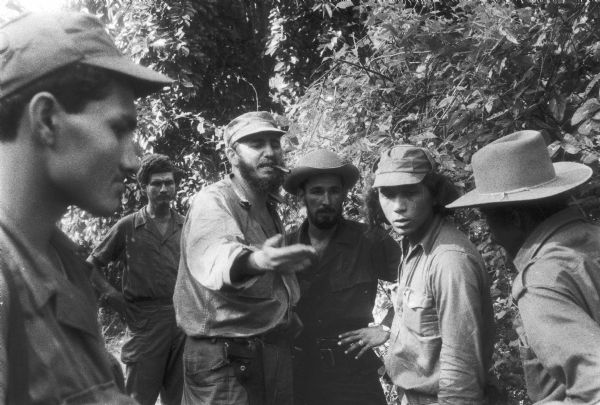 Fidel Castro with cigar, and five other men.