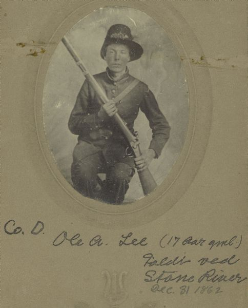 A seated studio portrait of Ole A. Lee, a private in Company D, 15th Wisconsin Infantry, in uniform, holding a musket across his chest.  The following information was obtained from the Regimental and Descriptive Rolls, Volume 20: He resided in Mt. Horeb, Wisconsin.  On February 10, 1862, he enlisted in Mt. Horeb, Wisconsin and on February 11, 1862, he was mustered into service in Madison, Wisconsin at the age of 17. He was killed in battle near Murfreesboro, Tennessee on December 31, 1862.