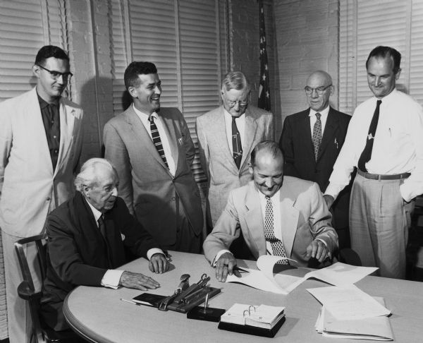 Frank Lloyd Wright (seated left), Madison Mayor Nestingen (seated right), and other officials signing a contract between the city of Madison and the Frank Lloyd Wright Foundation.