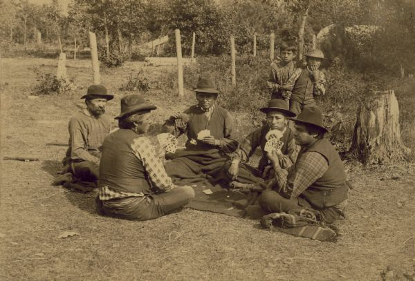 Five Winnebago men are sitting on the ground around a blanket playing cards. Two young boys are standing behind them watching.