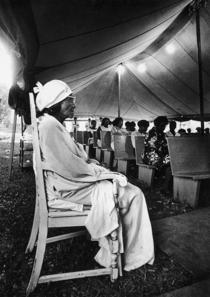 Willie Mae Small, 107 years old, sits in a chair off to the side during an outdoor service (church?).