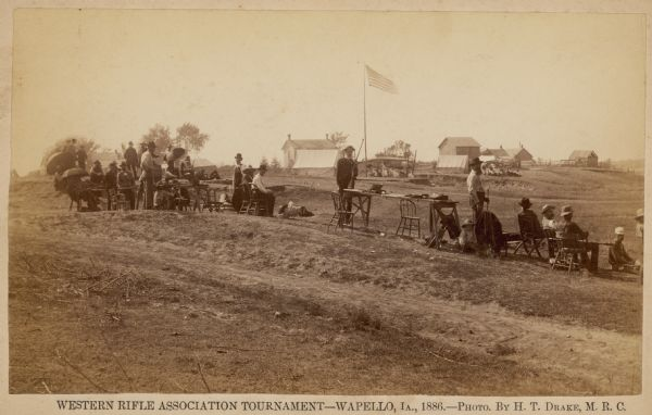 Men and boys participate in the Western Rifle Association Tournament.  Many of the participants are sitting under umbrellas and holding their guns.  Several tents of spectators are in the background.