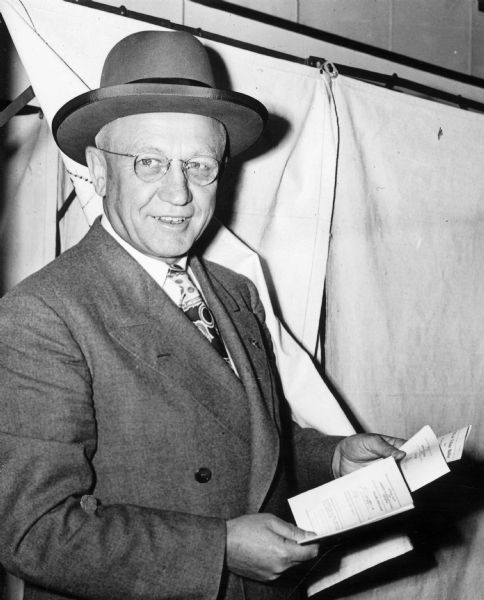 Governor Oscar Rennebohm outside a voting booth at the Maple Bluff village hall.  At the time, the Governor's Residence was located at 130 E. Gilman Street, but Rennebohm, the wealthy founder of Rennebohm Drug Stores, Inc., owned a large house in the exclusive village of Maple Bluff.  In 1949 the state purchased a new executive residence in Maple Bluff.