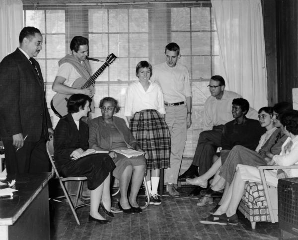 Eleven people, including Thurgood Marshall, Anne Braden, Myles Horton, and Septima Clark, are seated and standing during a Civil Rights meeting at Highlander School. Guy Carawan holds a guitar.