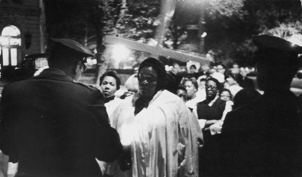 "Members of the National Welfare Rights Organization, some dressed in choir robes, hold candles and a cross as they are confronted by police. This is at the entrance to the United States Capitol where the group held a vigil in memory of Dr. Martin Luther King, Jr. after his assasination. Thirty-five of the NWRO leaders and three ministers were arrested for ""assembling to sing and pray""."