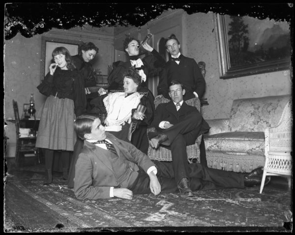 Group of people in dormitory or fraternity house. Four girls and three men inside room. One girl has a guitar and the other a small megaphone.