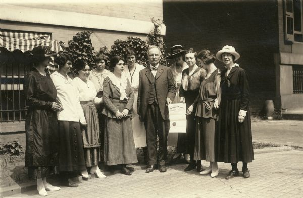 Former Wisconsin State Senator David G. James, Republican from Richland Center (1908-1912) and the father of suffragist Ada James. The photograph was likely taken June 13, 1919 after James delivered Wisconsin's ratification of the 19th Amendment in Washington, DC. James is surrounded by suffragists at the National Woman's Party headquarters building at 14 Jackson Place. The document he is holding is his appointment by Governor Philipp as Special Courier to deliver the ratification.
