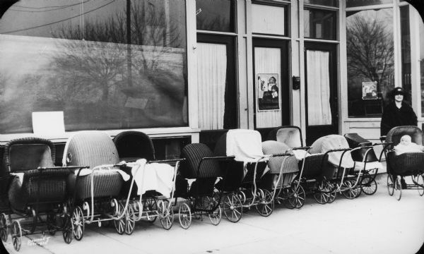 A mother and infant in a baby carriage pose at the end of a row of wicker baby carriages in front of what is probably the Neighborhood House.