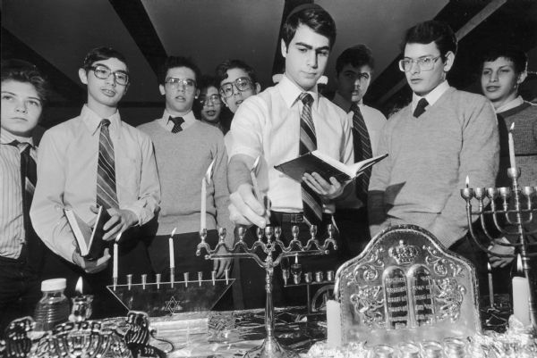 Hanukkah Ceremony - Abraham Anton uses a servant candle, called the Shamas, to light the first candle of Hanukkah Tuesday night as fellow students watch at the Wisconsin Institute for Torah Study, 3288 N. Lake Drive. The Shamas may become the center candle or the top candle, depending on the style of the Menorah. Hanukkah, an eight-day Jewish festival, commemorates a miracle that occurred when a one-day supply of oil lasted eight days after Judas Maccabeus recaptured the temple at Jerusalem.