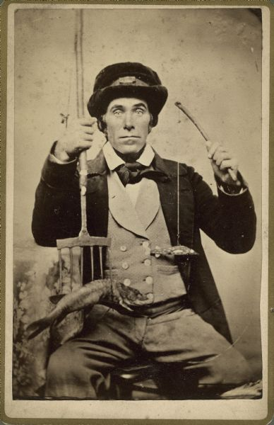 Studio portrait of a fisherman with his lure, spear, and catch.
