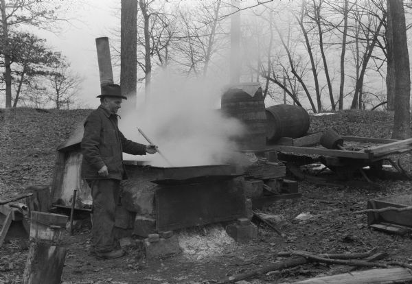 "Man in ""sugar bush"" (grove of maples) boiling down maple sap in production of maple syrup. Probably Wisconsin."