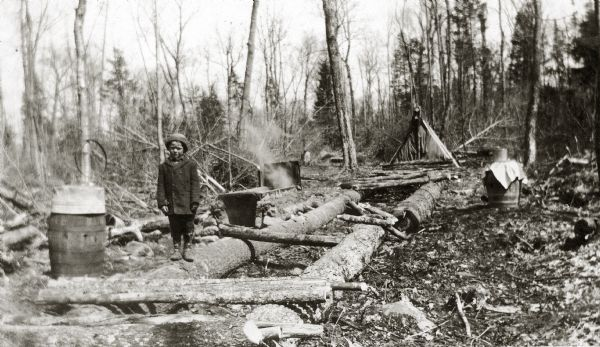 A child is standing on a log lying on the ground in a clearing. There is a barrel on the left, and a campfire in the background.