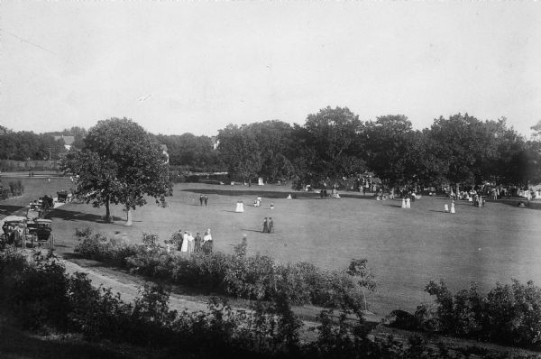 Elevated view of Vilas Park, filled with groups of people on the lawn, and horse-drawn carriages on the drive.