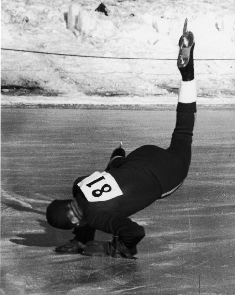 A Speed skater in competition falling onto the ice.