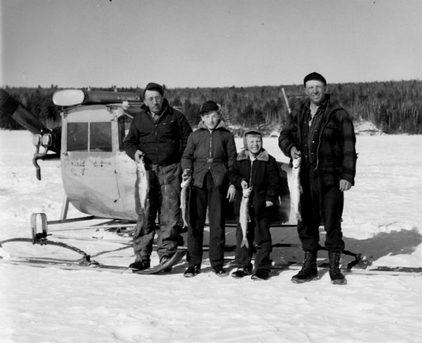 Two men and two boys standing on ice in front of a windsled. All four are holding lake trout.