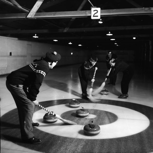 Curlers sweep in front of a stone during a curling match..