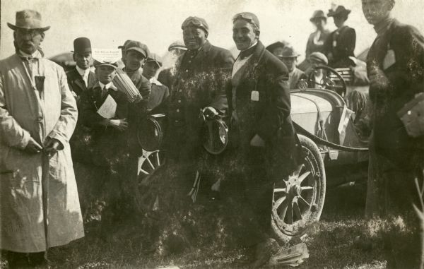 African American heavyweight boxing champion, Jack Johnson, drove up to Milwaukee from his home in Chicago to watch the Vanderbilt Cup race on October 2, 1912. A number of unidentified people are gathered around him as he and another man (both wearing goggles) lean against a car (probably Johnson's).