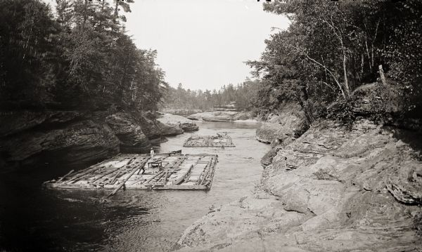 Two lumber rafts with men aboard floating down the Wisconsin River.
