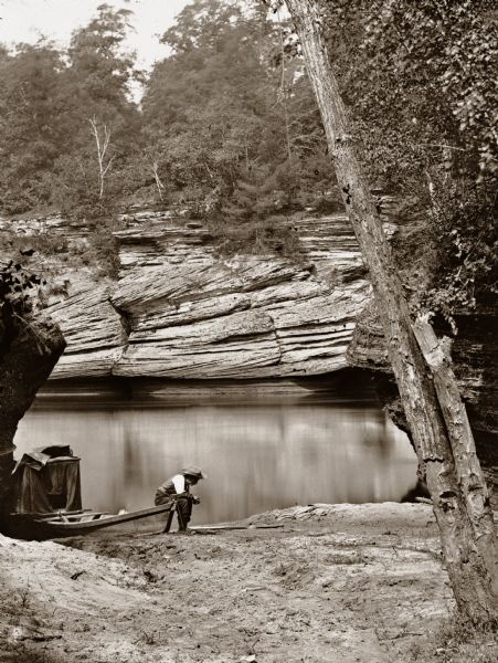 View up the river from behind Gates Ravine. There is a boat and dark tent at the edge of the river. H.H. Bennett is sitting on rowboat with his wetplate tent behind him.