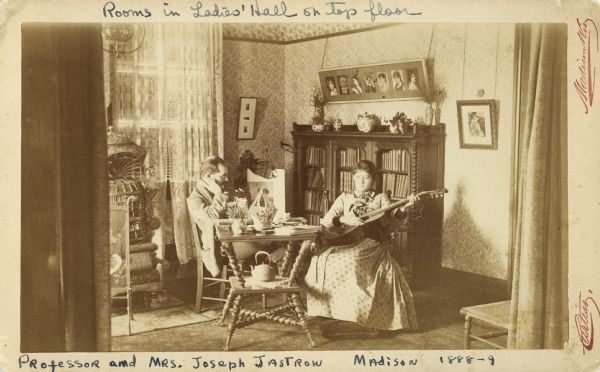 Professor Joseph Jastrow reading, and Rachel Jastrow playing guitar in a room on the top floor of Ladies' Hall (later Chadbourne Hall, razed 1957), in Madison, 1888-89.