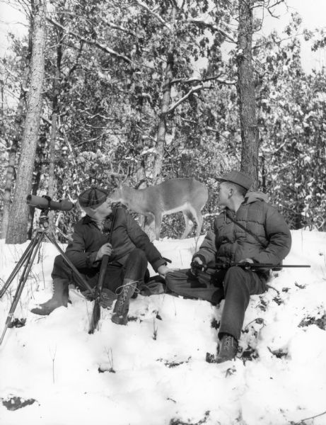 B. Olson and P. Helland sitting in the snow at a deer park in hunting gear, looking at a deer behind them.