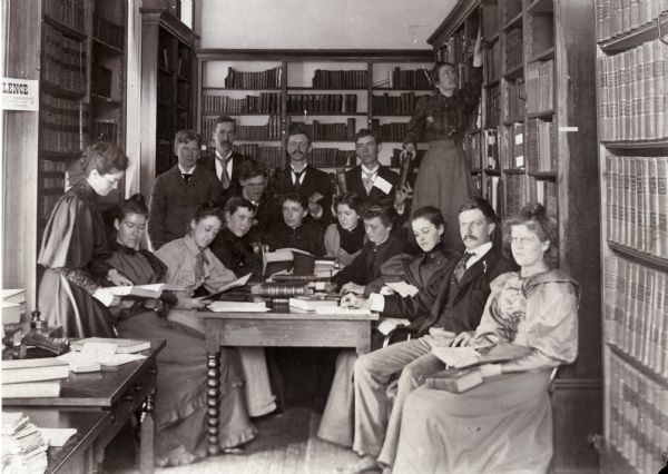 Frederick Jackson Turner with his History Seminar in an alcove of the Historical Society rooms in the third Wisconsin State Capitol, about 1893-1894. Back row, from left: W.B. Overson, J.M. Johnston, Joseph Schafer, Charles L. Baldwin, and Florence Baker Hayes (staff).  Front row, from left: Emma Hawley (staff), Estelle Hayden, Kate Bucknam, Ada Taylor, Annie Pellow, Dena Lindley, Sadie Bold, Flora Barnes, Turner, and Catharine Cleveland. The young man in the center, bending over, is E.F. Dithmar.