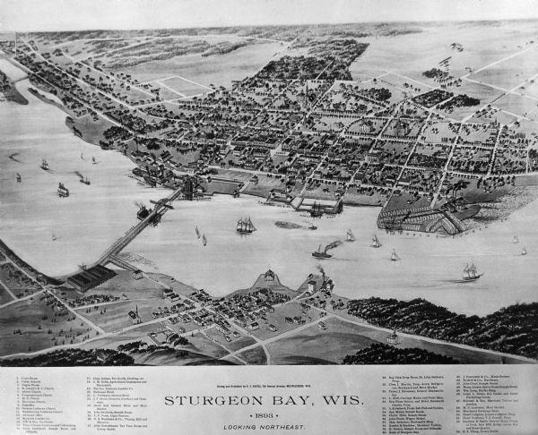Bird's-eye map of Sturgeon Bay, looking Northeast. Area bordered by Church Street in top left corner, leather & Smith Bridge in bottom left corner, Lawrence Street top right corner, and Main Street bottom right corner; one bridge spans water with many steam and sailing ships.  Fifty-three locations identified in location key below image.