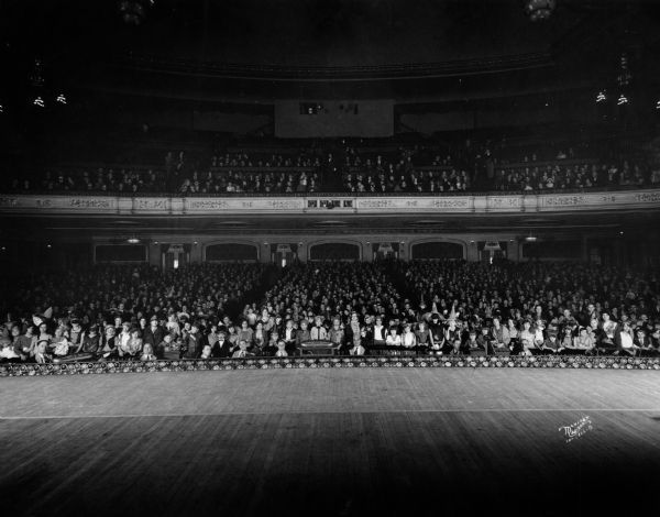 View from the stage of a full audience of costumed Halloween party-goers in the auditorium at the Orpheum Theatre, 216 State Street.