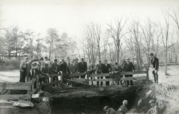 A group of well-dressed men gather at the digging site at Interstate Park.
