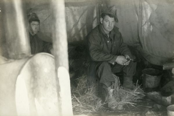 Two men seated inside a tent at the digging site at Interstate Park.