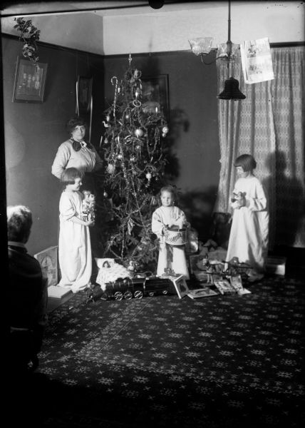 Family grouping at Christmas tree. From left, J. Robert Taylor's wife, Alma Reinhardt Taylor, daughter Donna, son Frederick, and daughter Ellen.