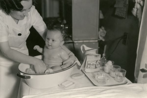 Dr. Hunter of the Wisconsin Board of Health bathes a baby in a tub of water.