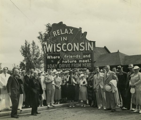 "Group of resort and hotel owners gathered in front of a Wisconsin tourism sign that reads: ""Relax In Wisconsin."" There is a building in the background."