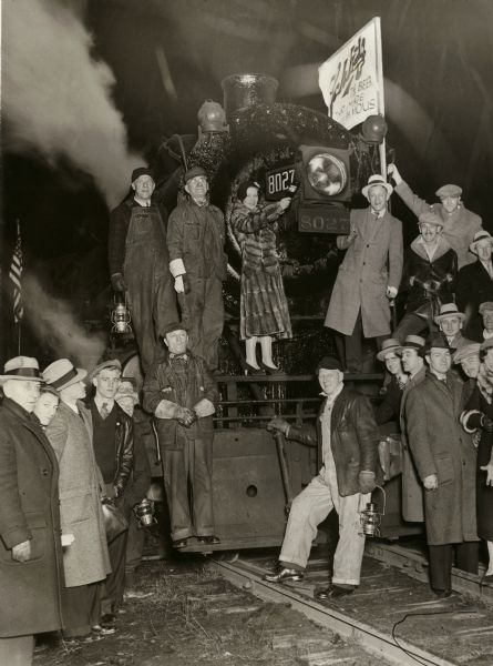 Schlitz train and group of revelers, celebrating the end of prohibition in Milwaukee. Schlitz Engine #8027 departs to deliver the first Schlitz beer at 12:01 a.m. on April 7, 1933. Pictured from left are R.D. Miller, Superintendent; (on front footboard) Jesse Worner, Yardman; (in front of draw casting) A. Basta, Fireman; Edward Wroblewski, (on running board above front beam) Anton Plewa, Conductor; (between Conductor and woman) and William H. Kay, Engineer.