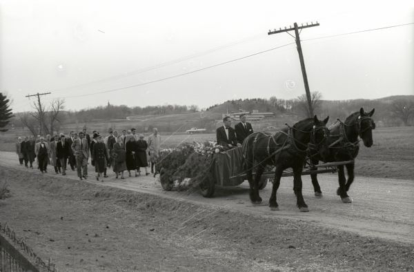 Funeral procession of Frank Lloyd Wright to Unity Chapel Cemetery. His body is carried in a horse-drawn vehicle with a group of people marching behind.