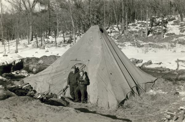 Tent covering the excavation site of the bones of extinct bison. Milo Mickelson and Lester Giesler are standing in the doorway of the tent.