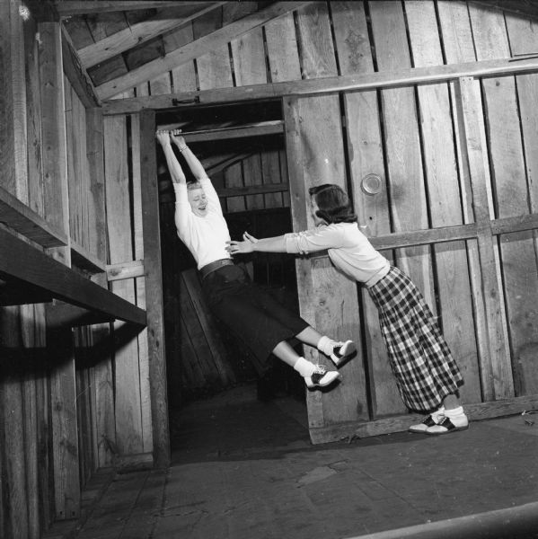 Harriet Anderson (whose name has since changed to Penny Hilley) and Nancy Waterman clowning around at the Wonder Spot in Lake Delton in the Wisconsin Dells. Nancy hangs at an angle in the doorway.
