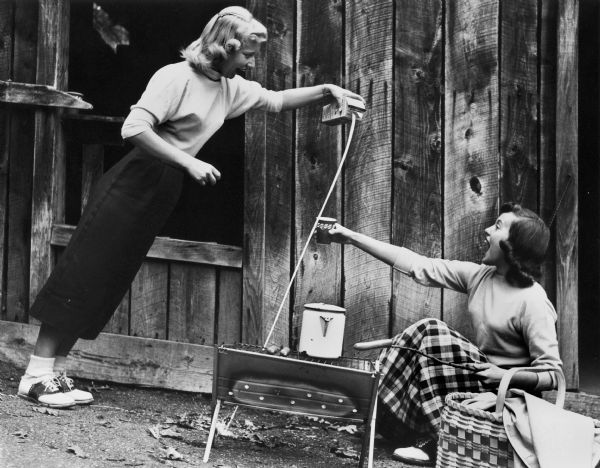 Nancy Waterman unsuccessfully pours milk for Harriet Anderson (whose name has since changed to Penny Hilley) at the Wonder Spot.