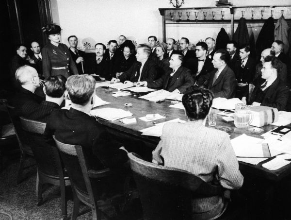 A woman stands before an assembly committee meeting in an executive session.