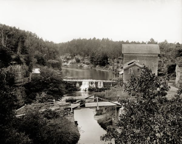 Elevated view of Mirror Lake Mill with bridge in foreground. Two women stand on the bridge looking down at the river.