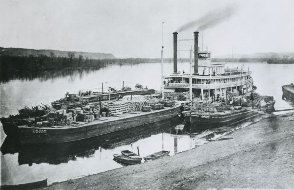 "View down hill towards ""Diamond Jo"" steamboat docked on the shoreline of the Mississippi River while goods are being loaded onto the steamboat."